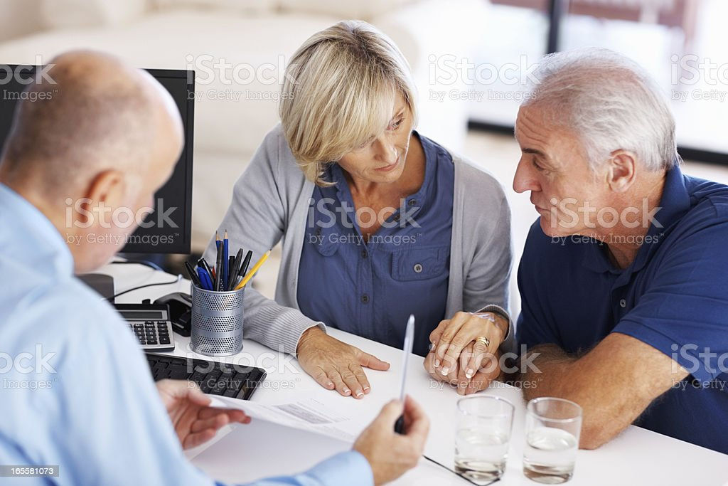 Senior couple looking at each other before signing the document stock photo