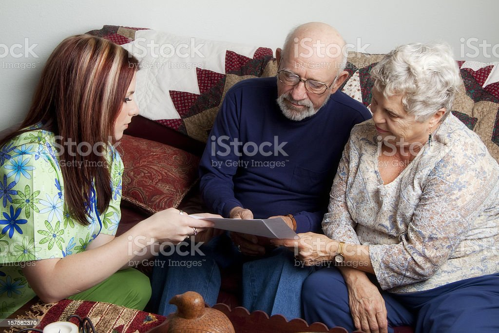 Senior couple looking at papers with young nurse in scrubs royalty-free stock photo