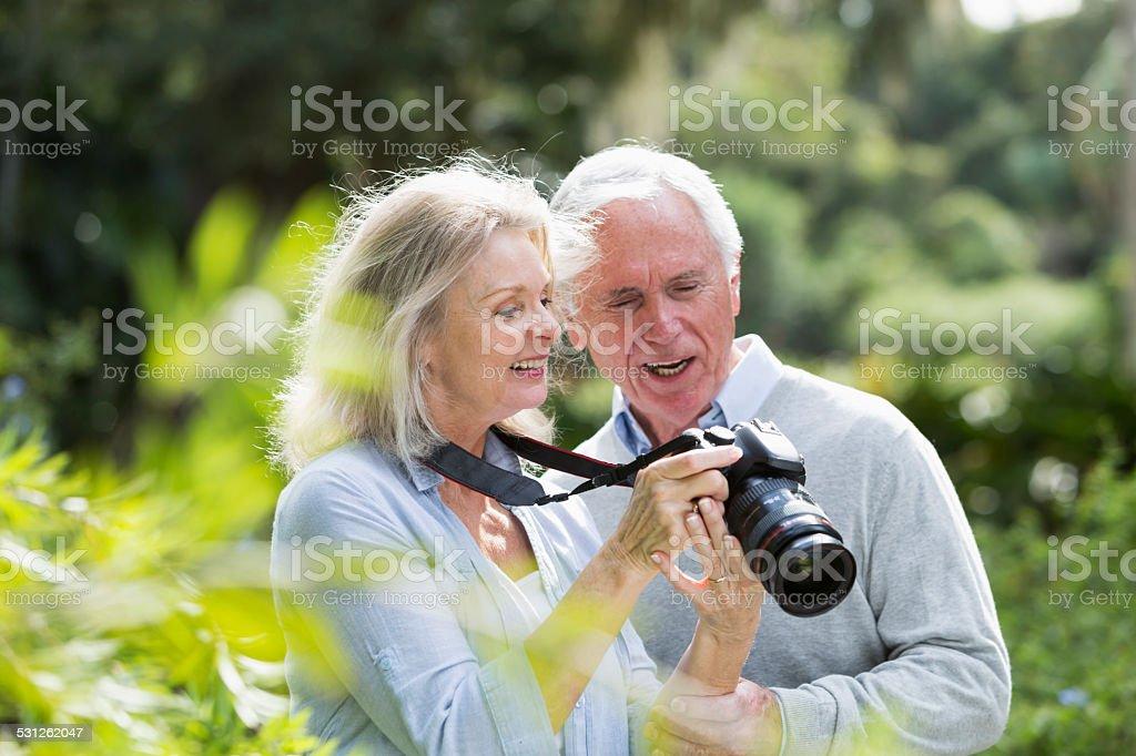 Senior couple looking at photos taken on camera stock photo