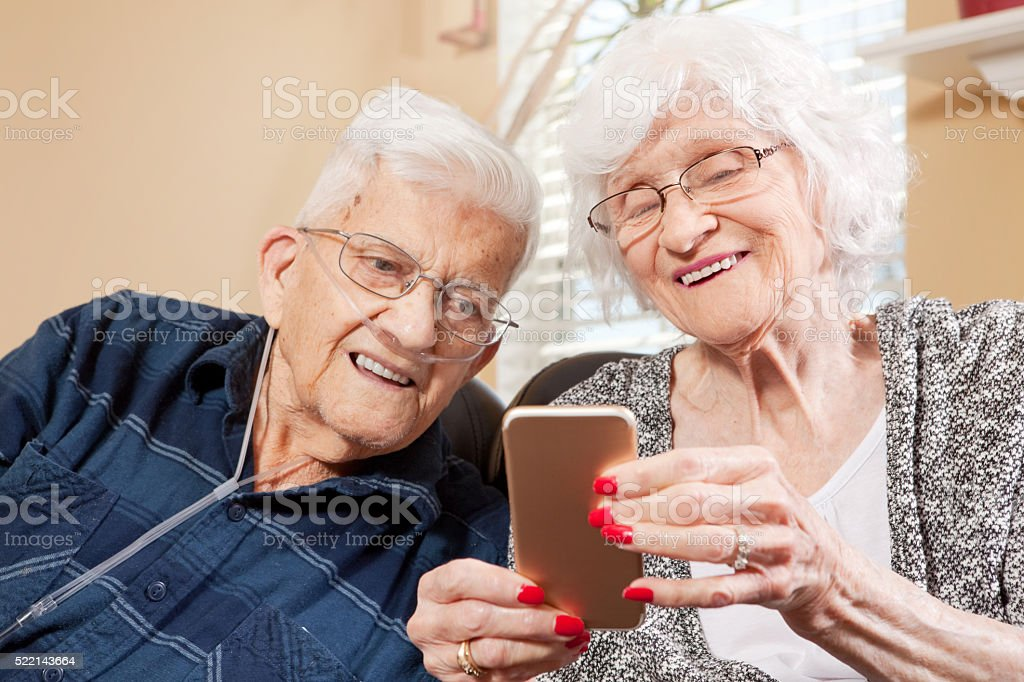 Senior Couple Looking At Smart Phone stock photo