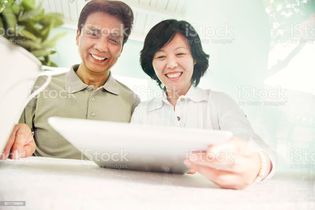 Senior couple looking at tablet computer stock photo