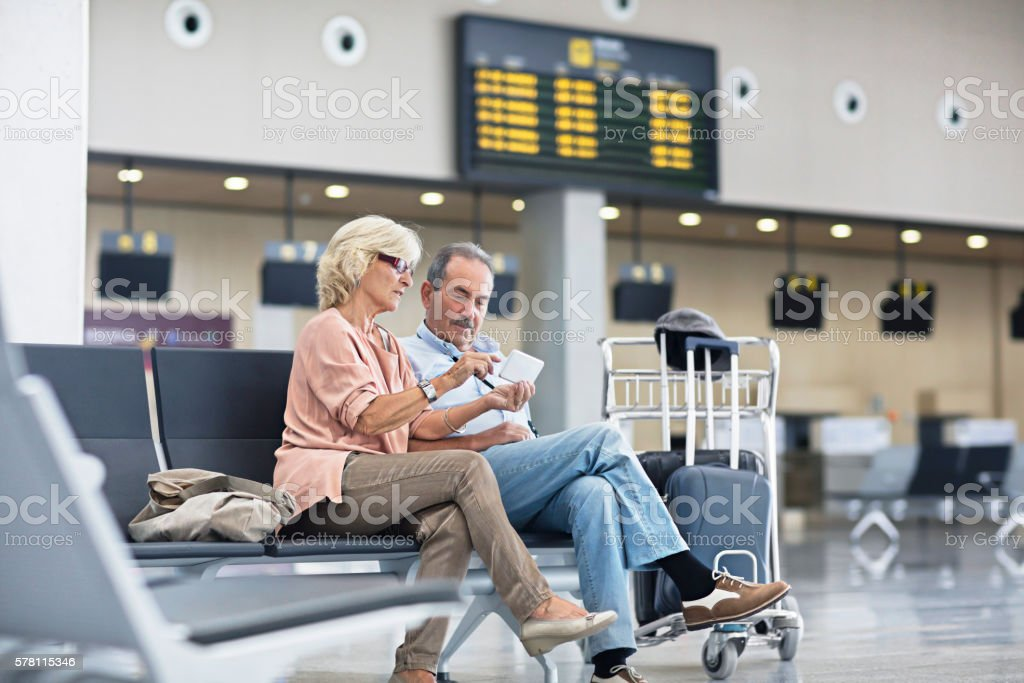 Senior Couple looking at the mobile phone at the airport stock photo