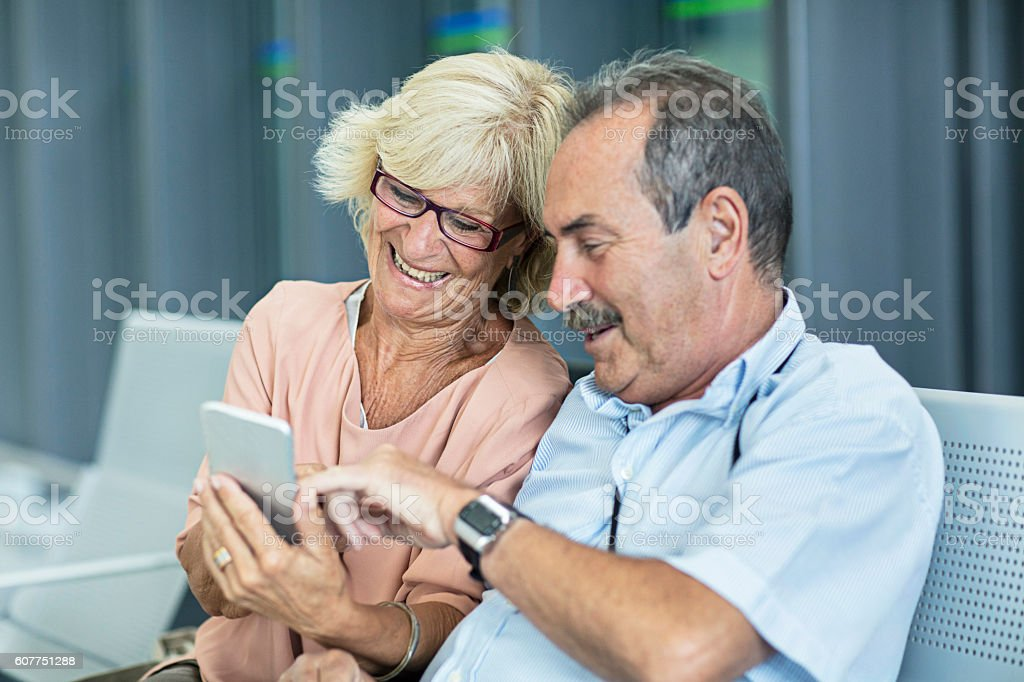 Senior Couple looking at the mobile phone stock photo