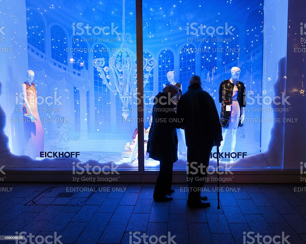 senior couple looking at window display of luxury clothing store royalty-free stock photo