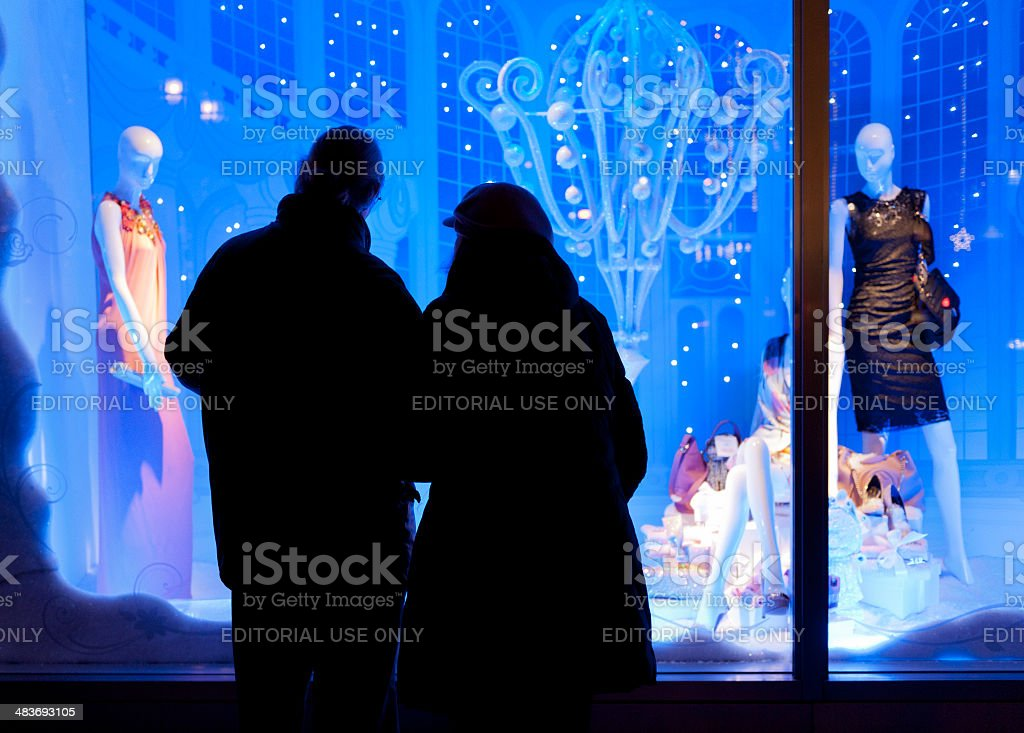 senior couple looking at window display of luxury clothing store stock photo