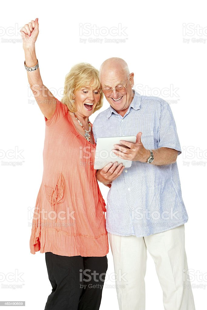 Senior couple looking excitedly at digital tablet royalty-free stock photo