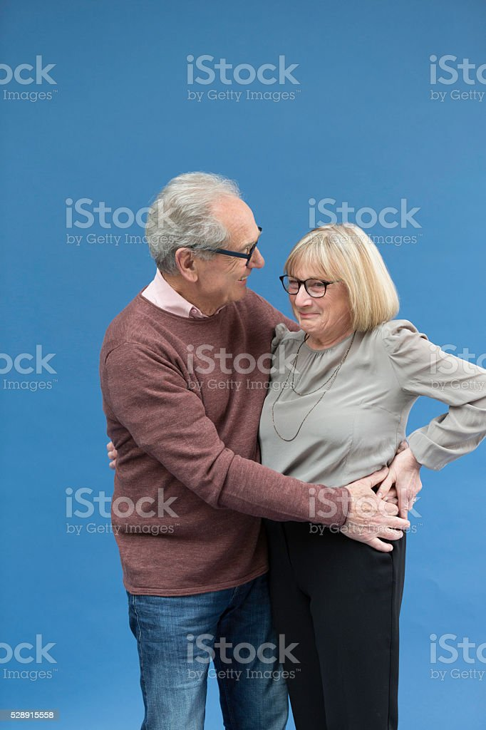 Senior couple looking lovingly and holding each hip stock photo