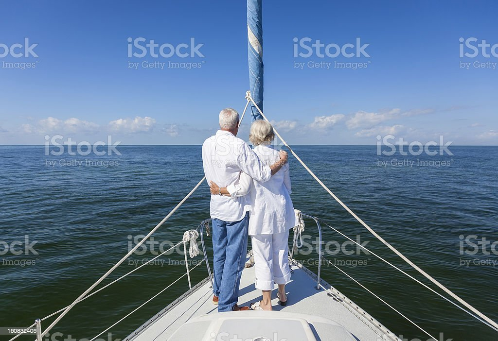 A senior couple looking out at the water on a sailboat royalty-free stock photo
