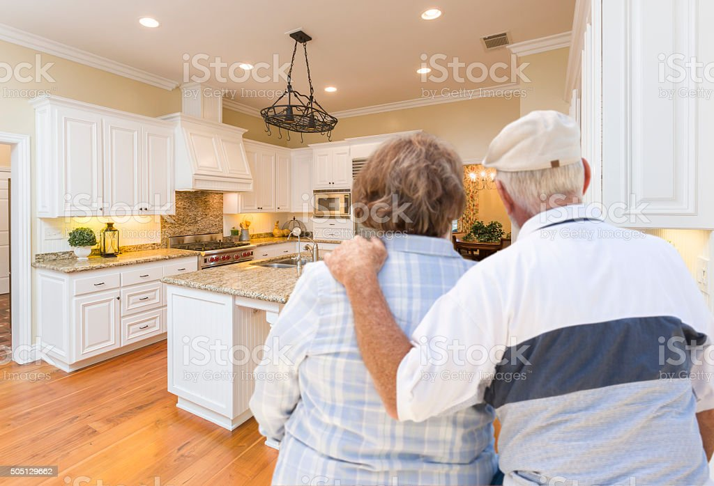 Senior Couple Looking Over Beautiful Custom Kitchen stock photo