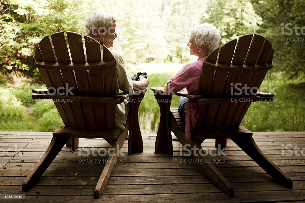 Senior Couple Lounging in Adirondack Chairs on a Wood Deck stock photo