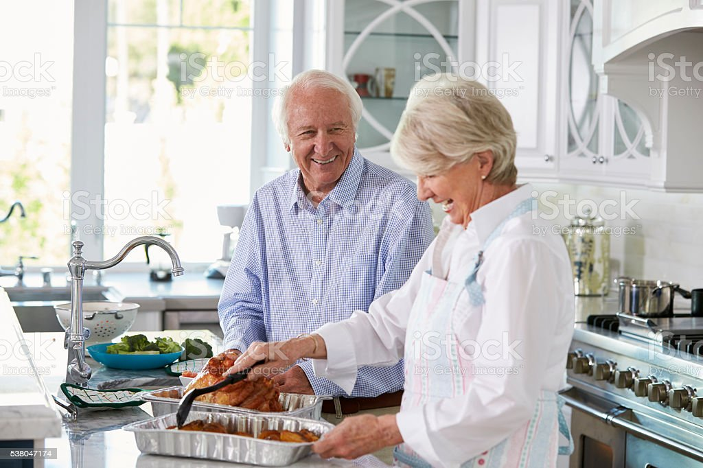 Senior Couple Make Roast Turkey Meal In Kitchen Together stock photo