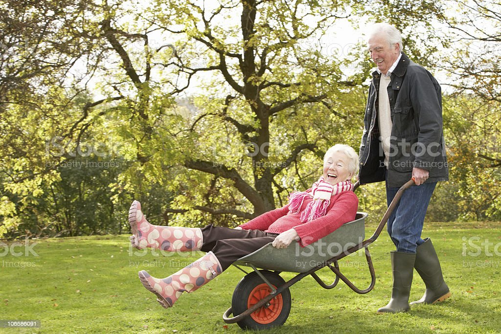 Senior Couple Man Giving Woman Ride In Wheelbarrow stock photo