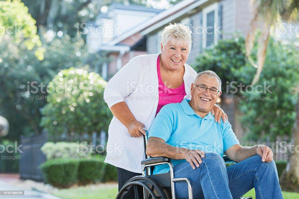 Senior couple, man in wheelchair getting fresh air stock photo