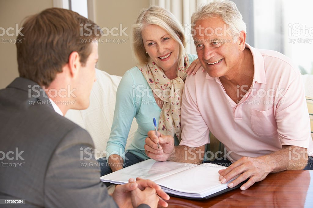 Senior Couple Meeting With Financial Advisor At Home stock photo