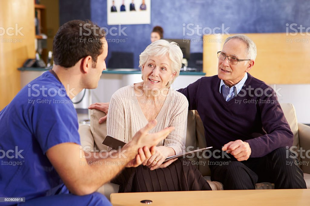 Senior Couple Meeting With Nurse In Hospital stock photo