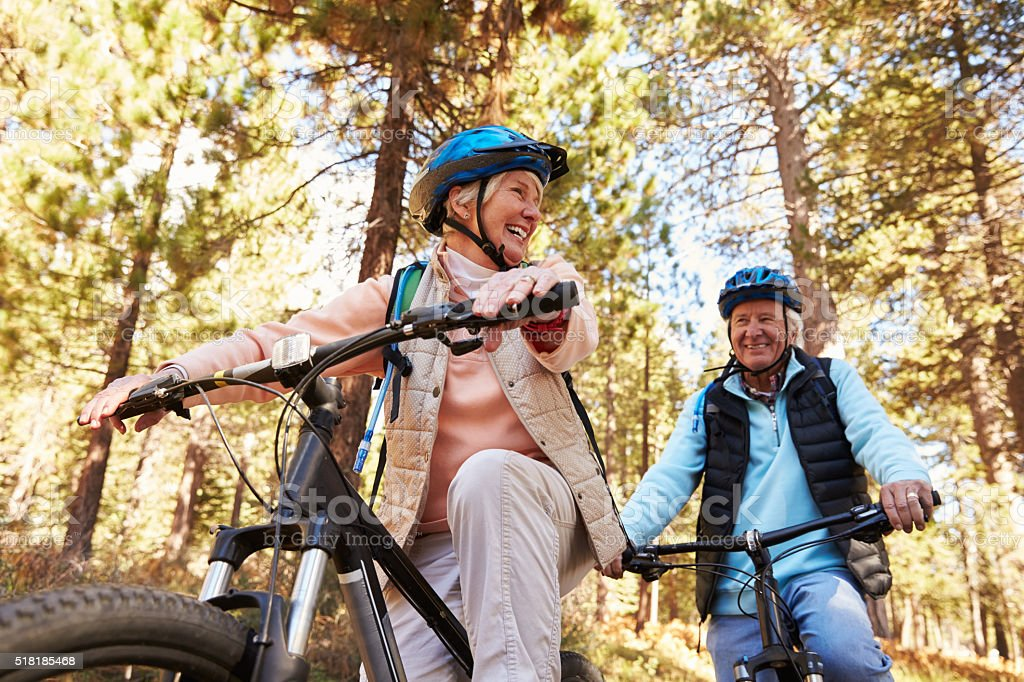 Senior couple mountain biking on a forest trail, low angle stock photo