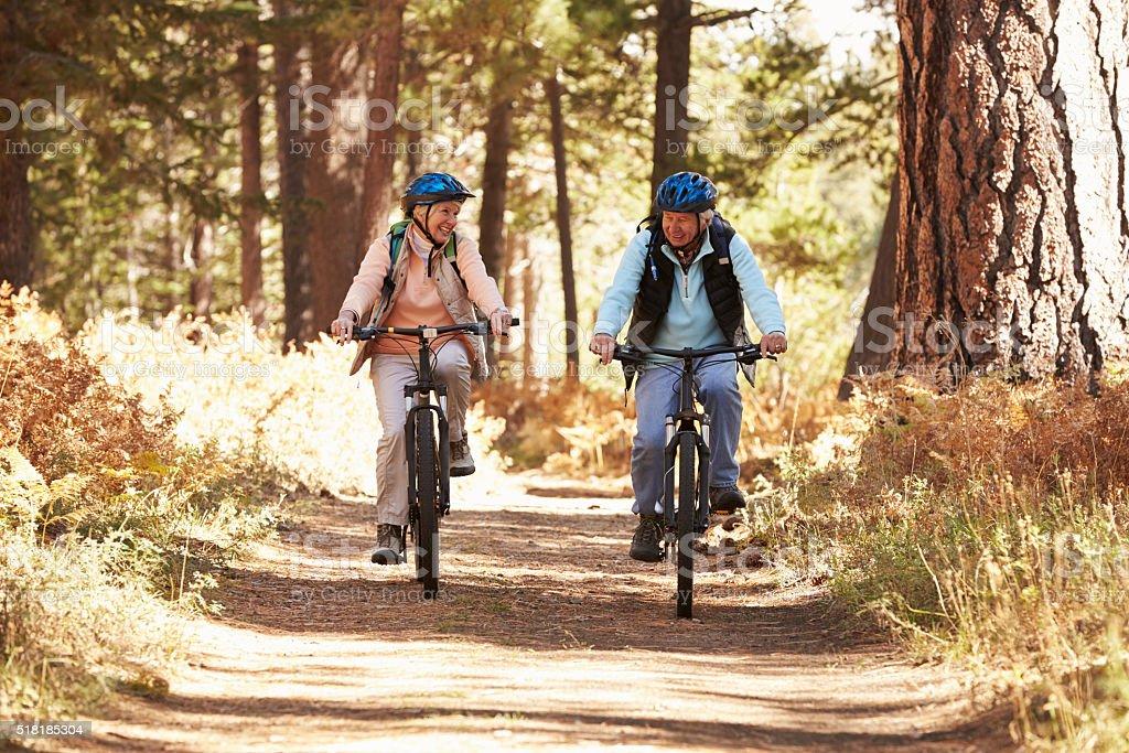 Senior couple mountain biking on forest trail, California stock photo