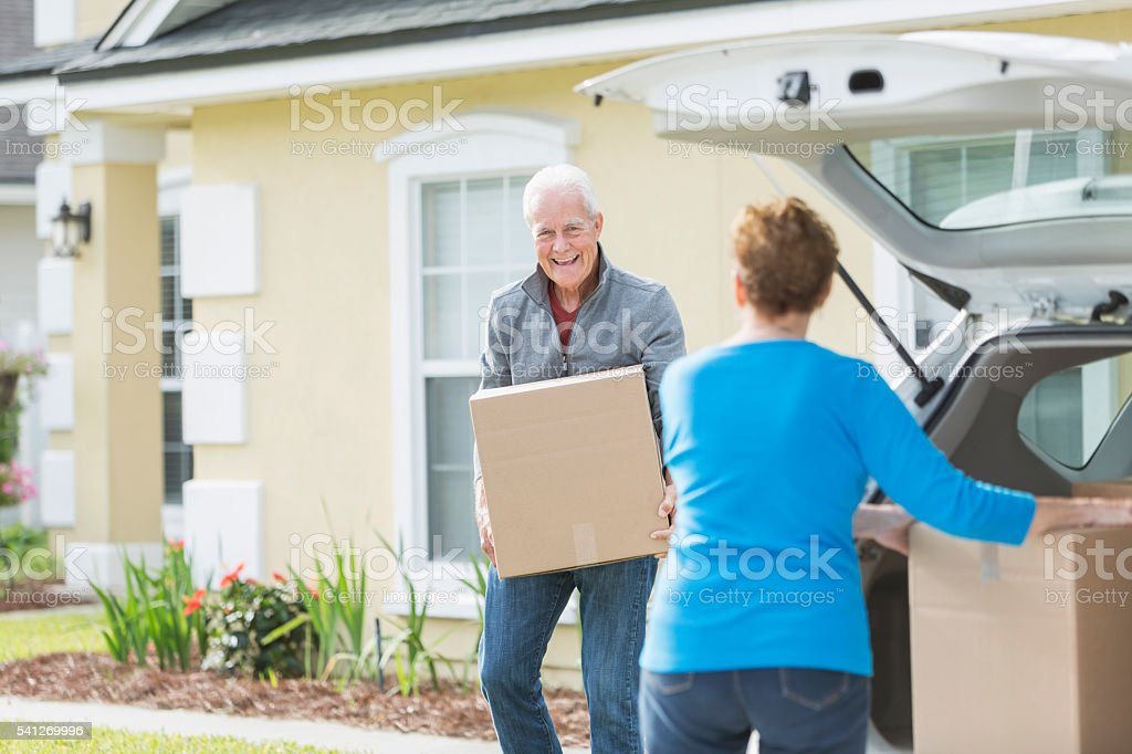 Senior couple moving boxes in trunk of car stock photo