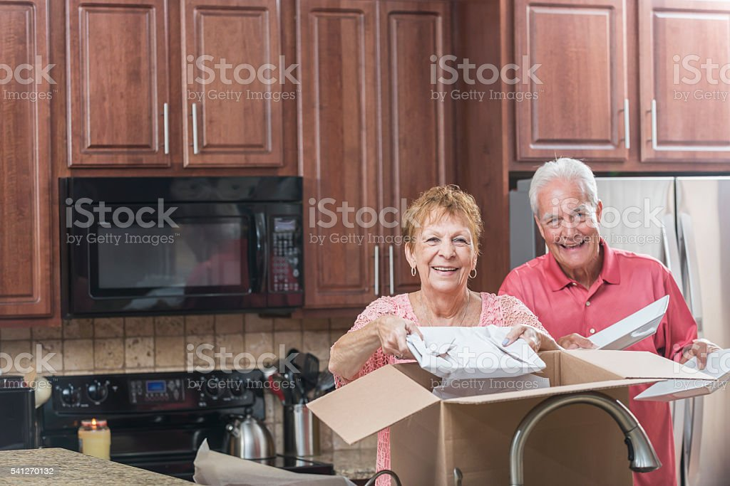 Senior couple moving house, in the kitchen stock photo