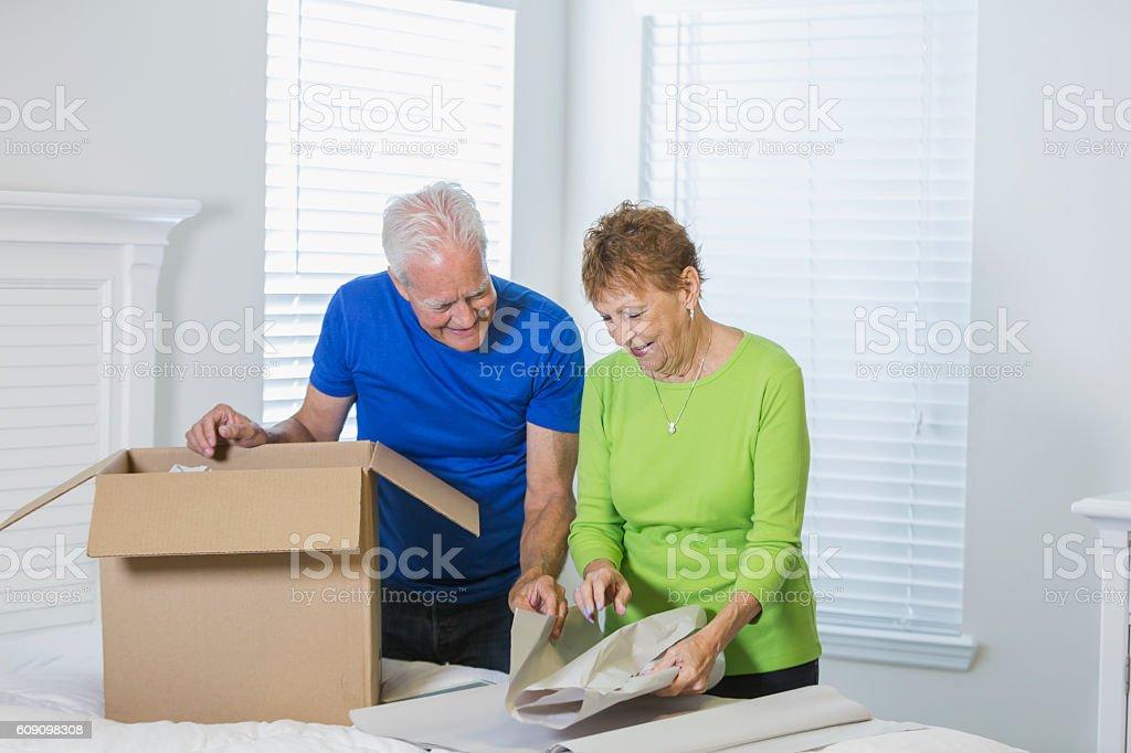 Senior couple moving house, packing box stock photo
