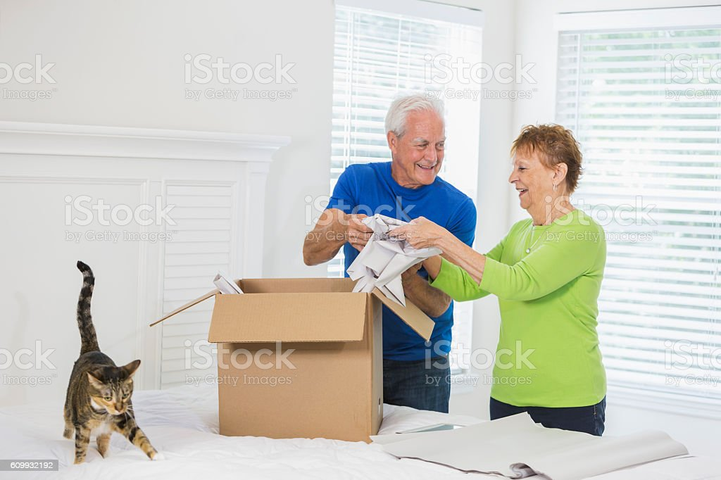 Senior couple moving house, packing box stock photo