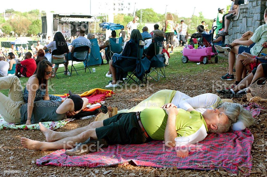 Senior Couple Naps On Blanket Among People At Atlanta Festival stock photo