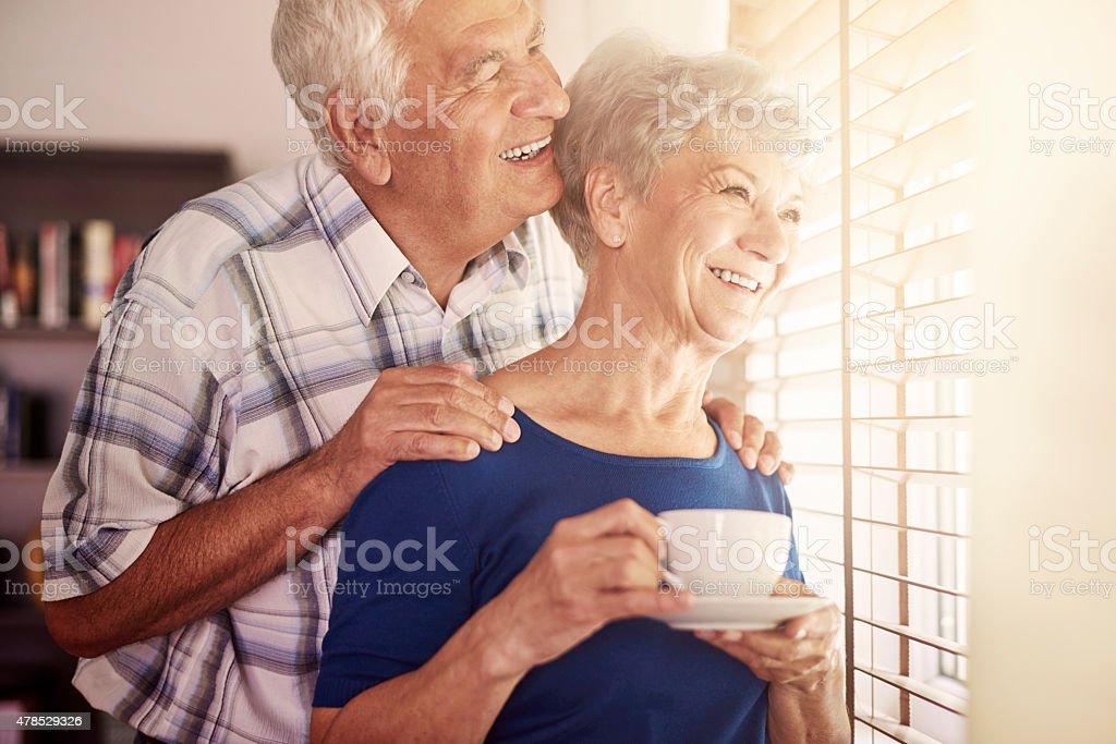 Senior couple next to the window stock photo