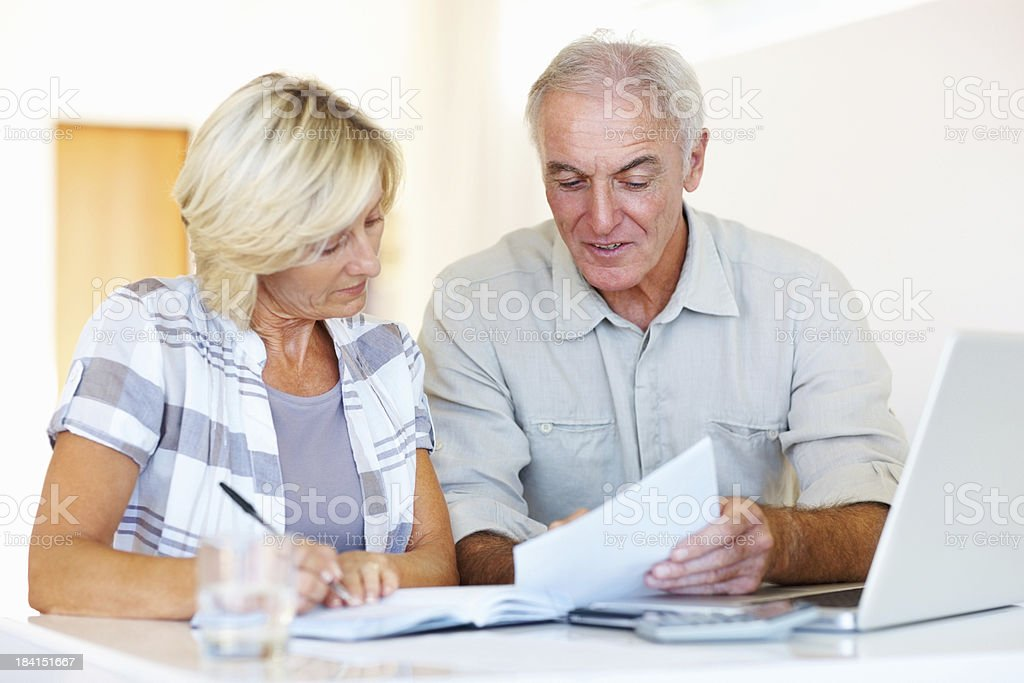 Senior man helping his wife for calculating their monthly expenses