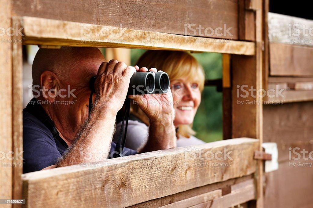 Senior couple observing wildlife through binoculars stock photo