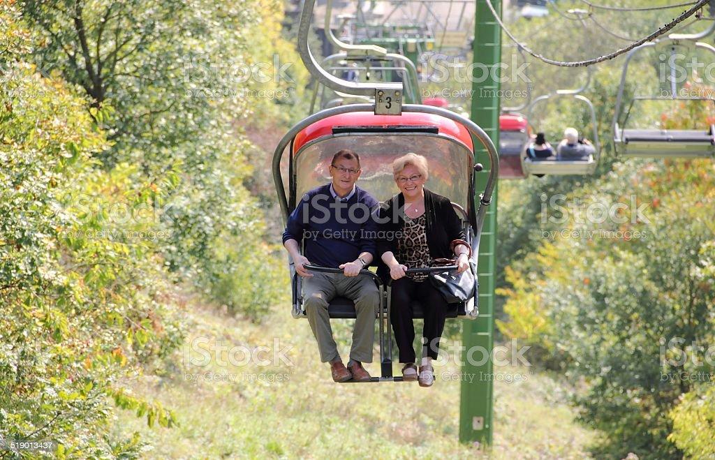 Senior couple on a chair lift enjoying landscape. stock photo