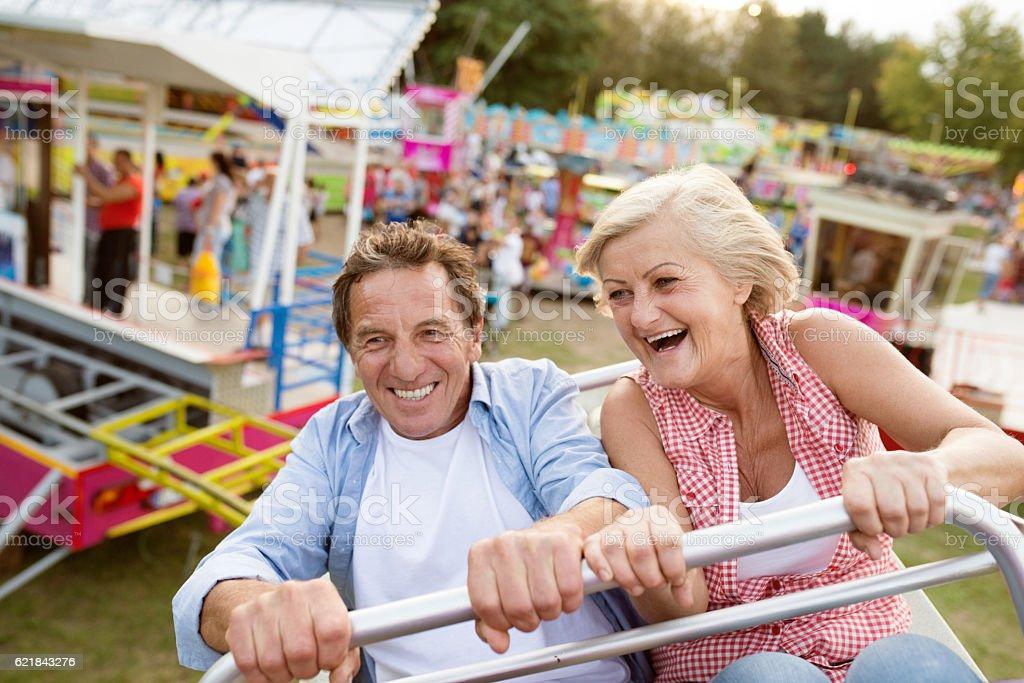 Senior couple on a ride in amusement park stock photo