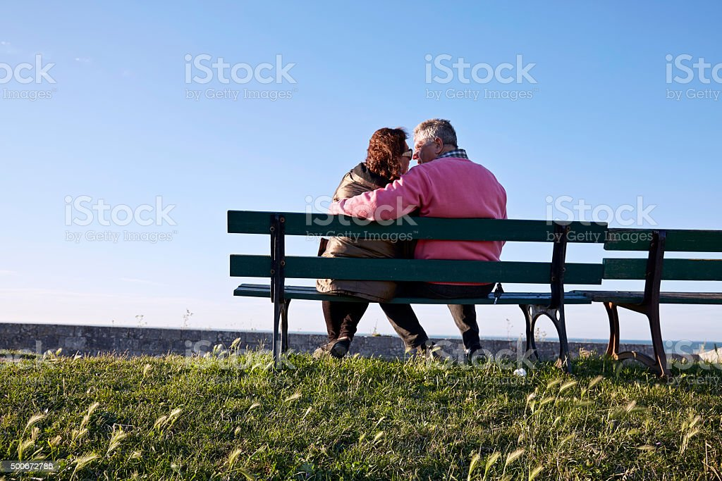 Senior couple on  bench at harbour sunset stock photo
