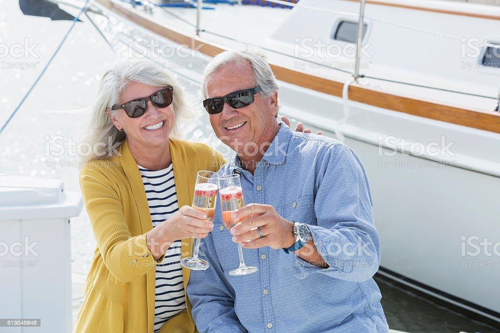Senior couple on boat celebrating with champagne stock photo
