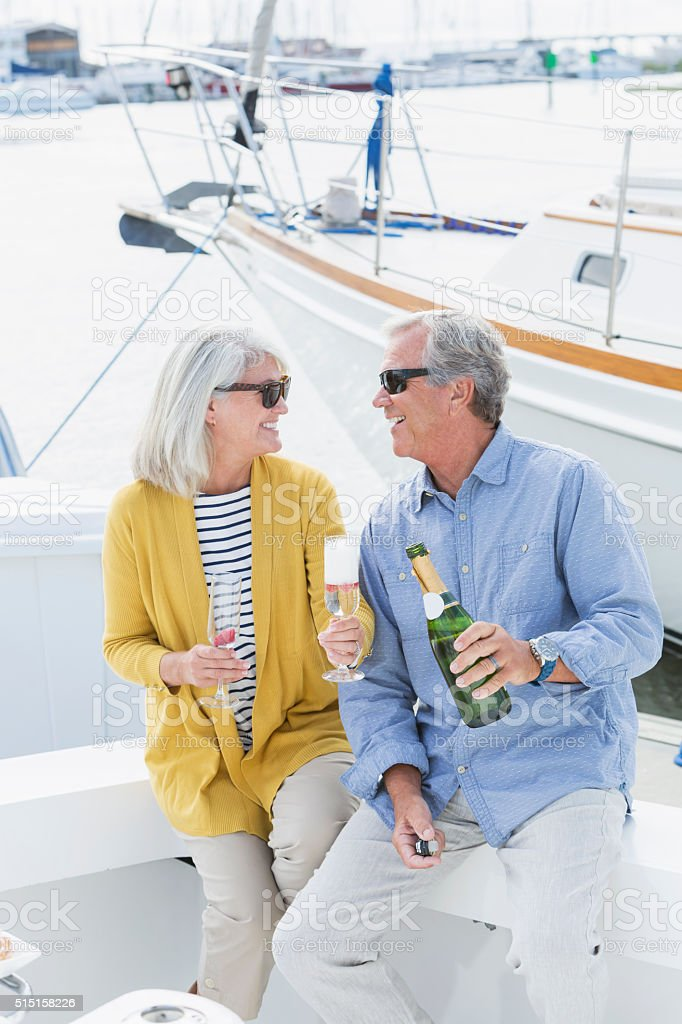 Senior couple on boat celebrating with champagne stock photo