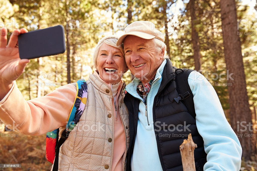 Senior couple on hike in a forest taking a selfie stock photo