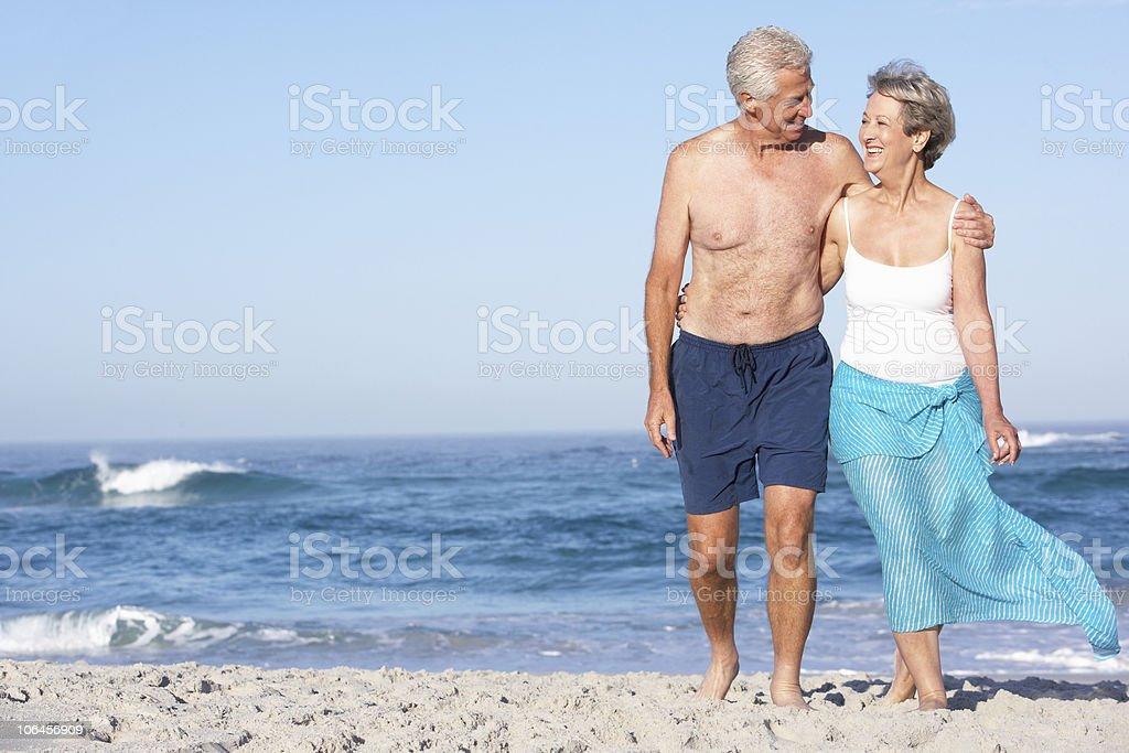 Senior Couple On Holiday Walking Along Sandy Beach royalty-free stock photo