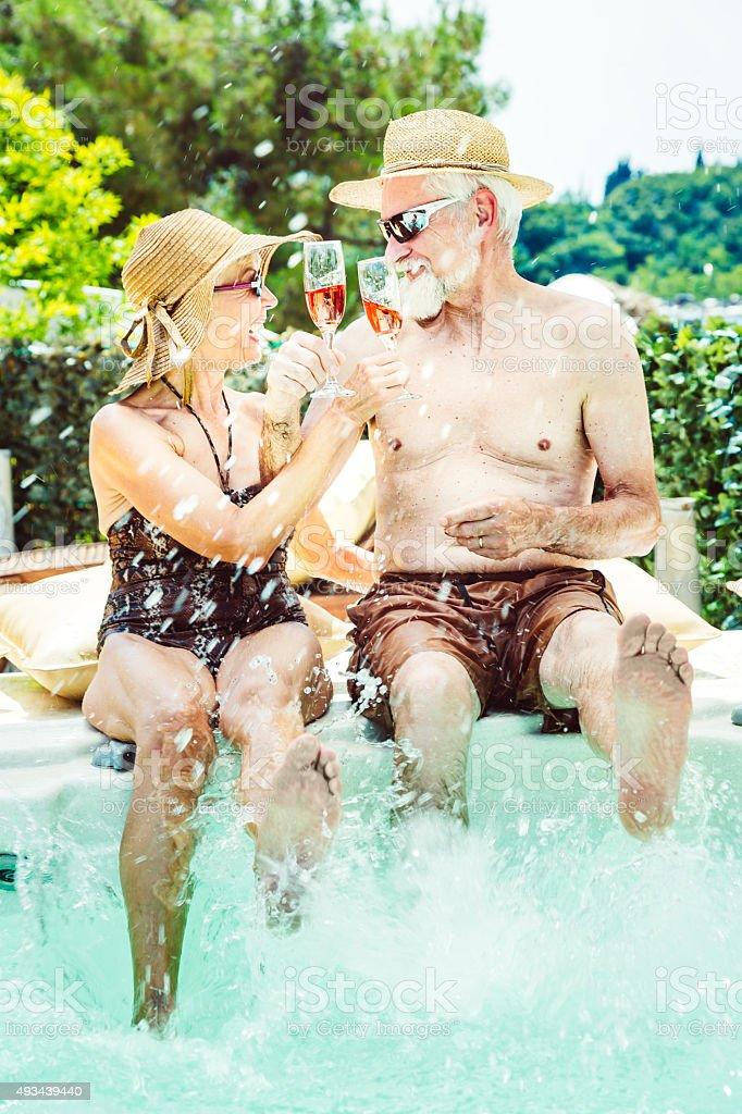 Senior couple on holidays having fun in jaccuzi toasting stock photo