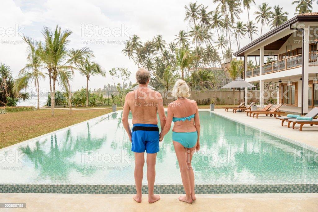 Senior couple on poolside in swimwear holding hands stock photo