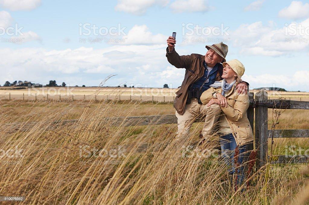 Senior Couple On Walk Taking Selfie On Mobile Phone stock photo