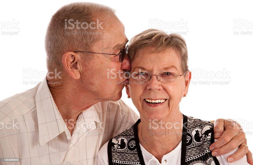 Senior couple on white background kissing royalty-free stock photo