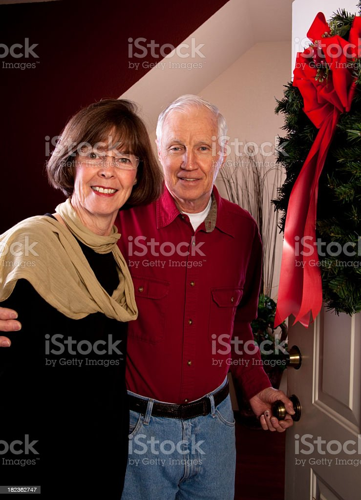 Senior couple  opening front door Christmas wreath royalty-free stock photo