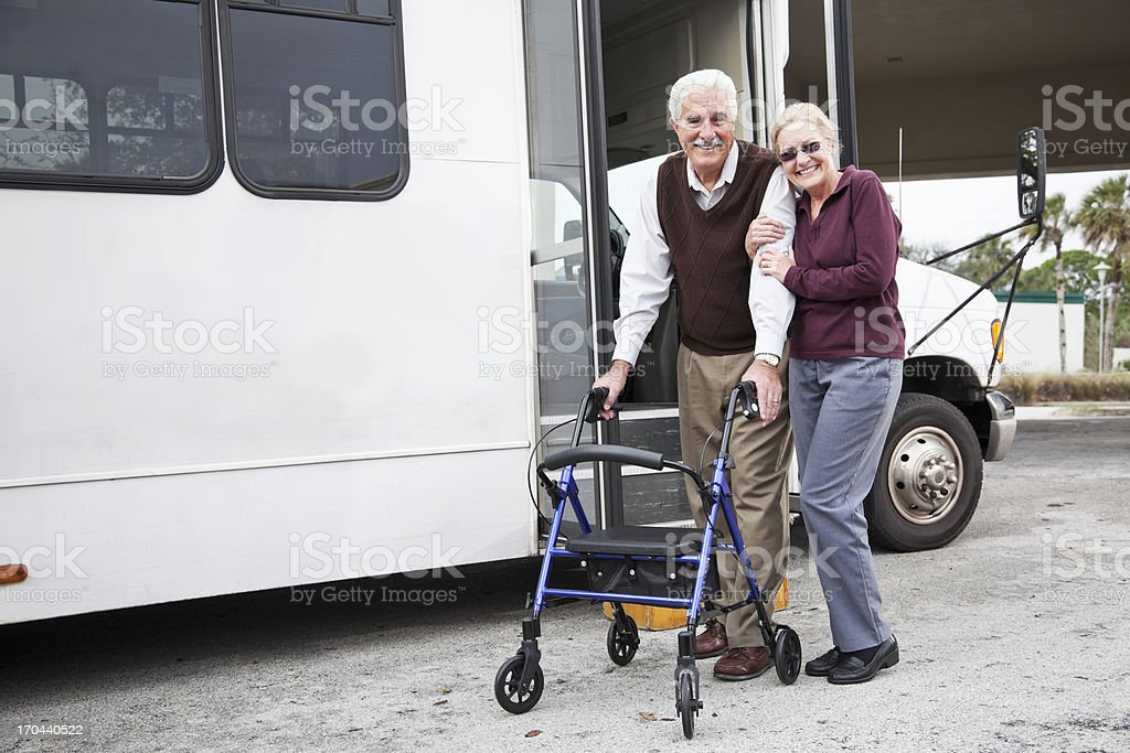 Senior couple outside shuttle bus stock photo