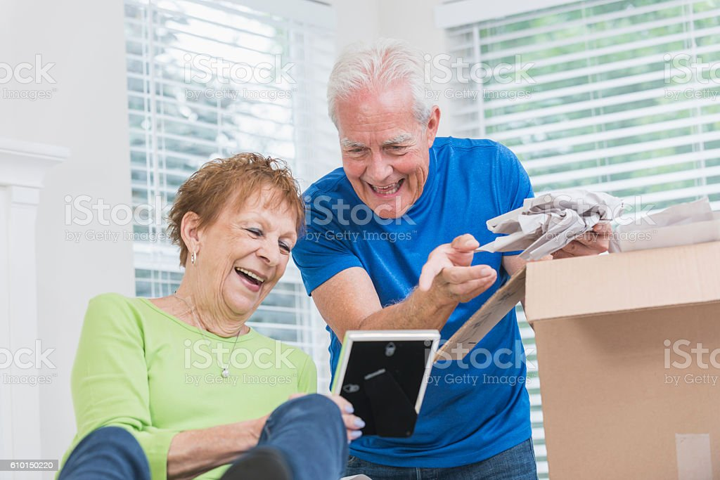 Senior couple packing box, looking at picture frame stock photo