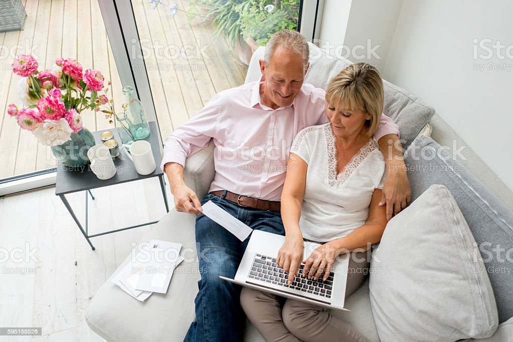 Senior couple paying bills online at home stock photo