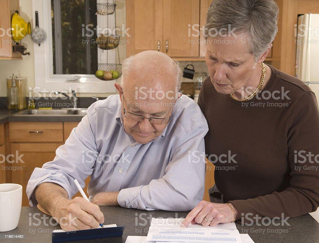 senior couple paying bills stock photo