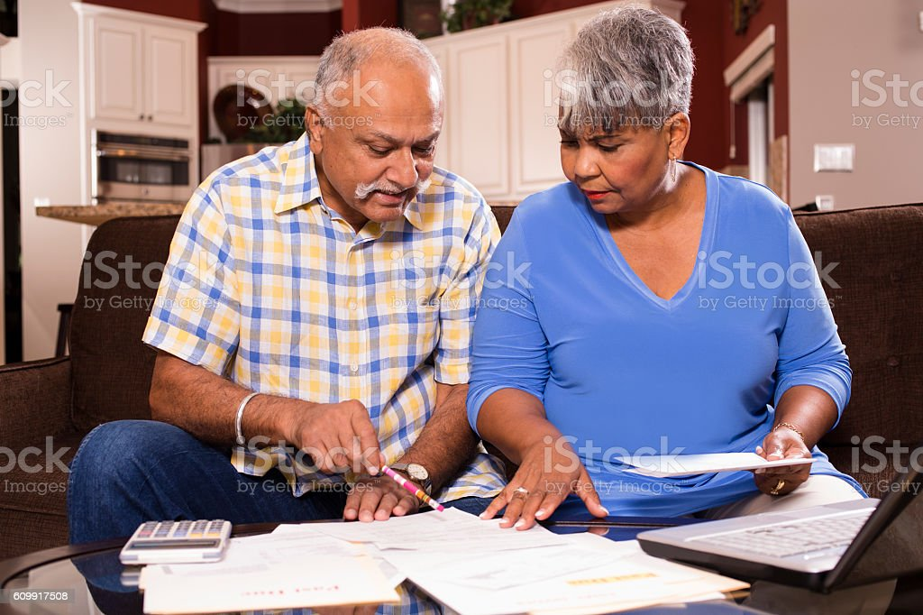 Senior couple paying monthly bills at home. stock photo