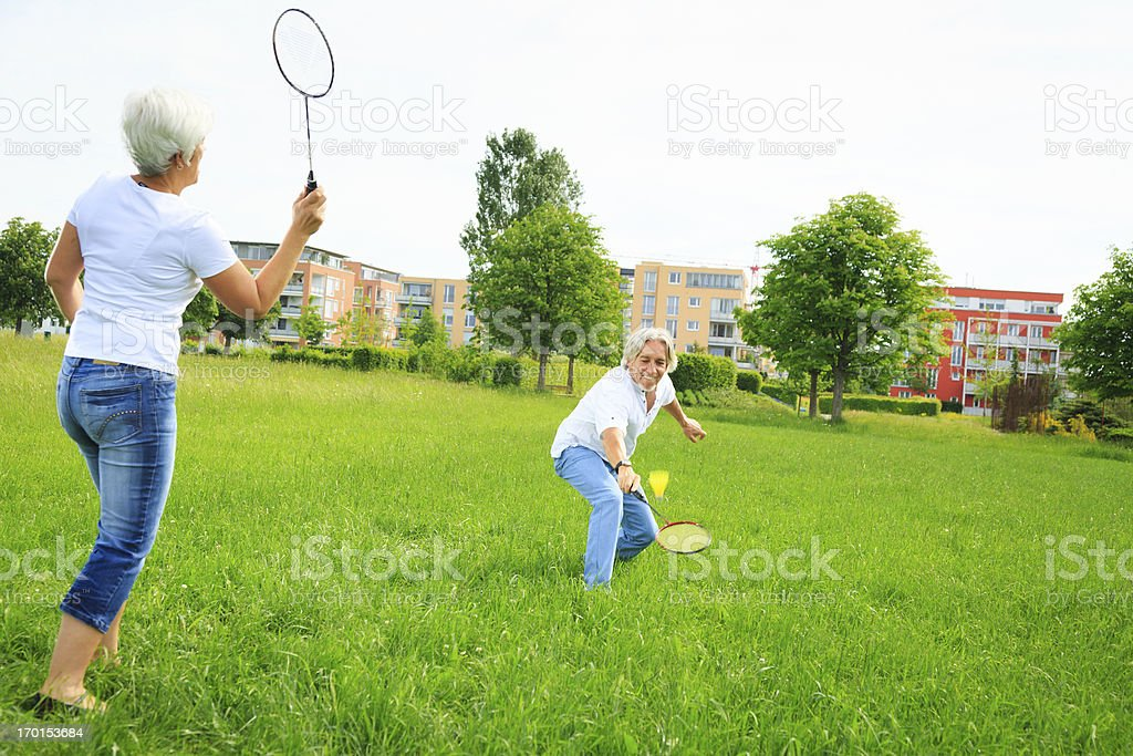 senior couple playing badminton stock photo