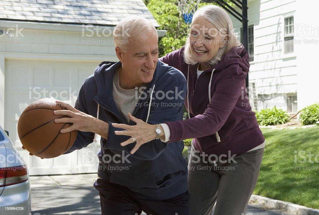 Senior couple playing basketball stock photo