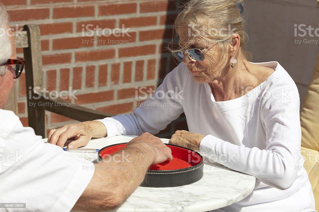 Senior couple playing dice game outdoor in garden. Yahtzee. stock photo