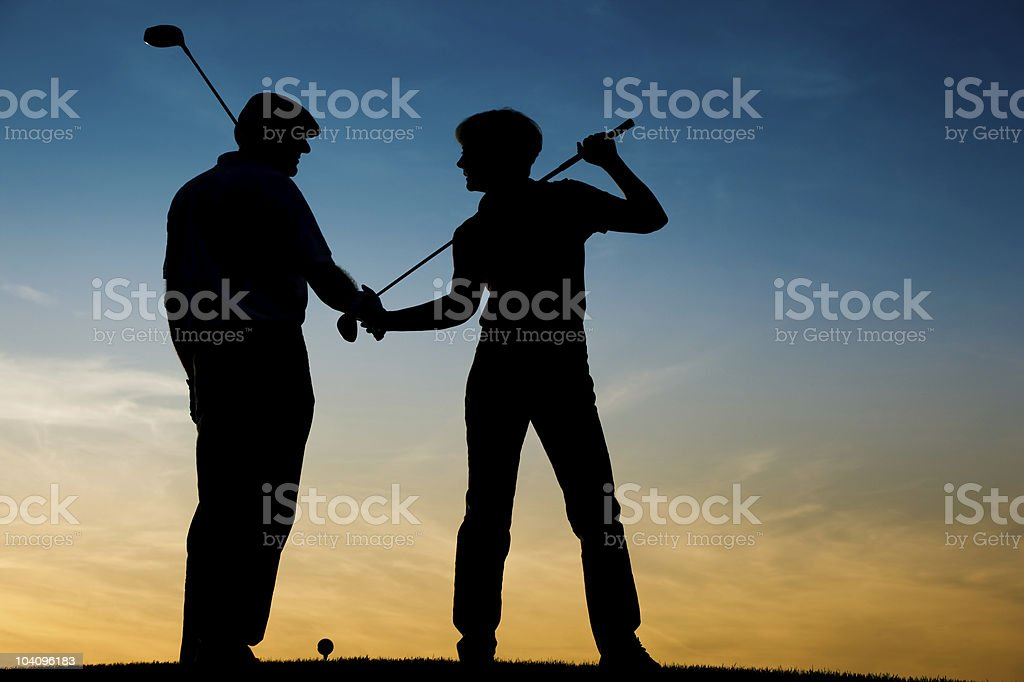 Senior couple playing Golf at sunset royalty-free stock photo